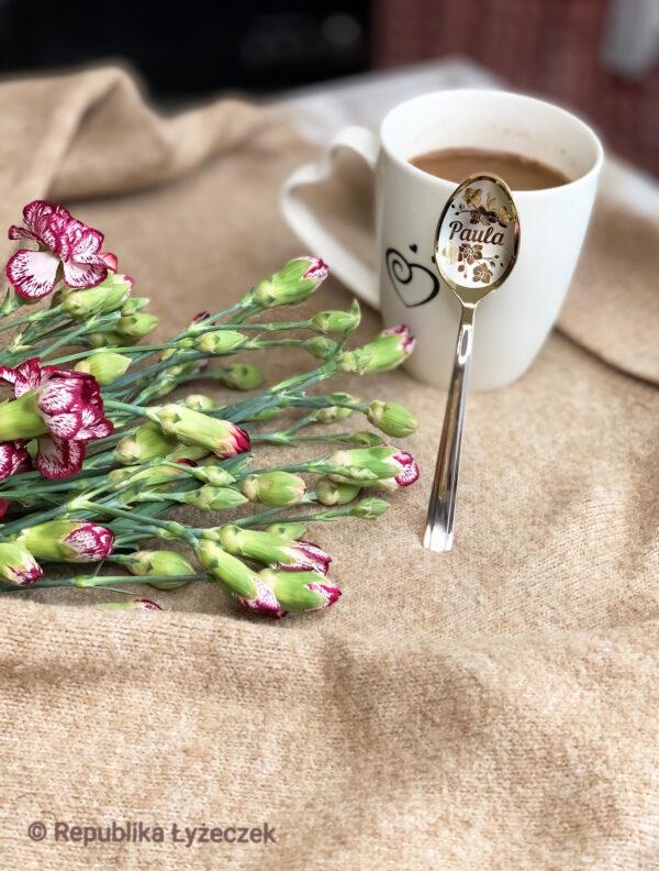 łyżeczka nierdzewna srebrne-złotego koloru z wygrawerowanym imieniem Pola opiera się na szklankę, obok kwiaty