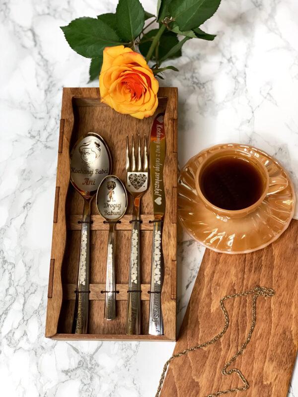 Zestaw sztućców w pudełku na prezent dla Babci z personalnym grawerem. szklanka z kawą i róża obok