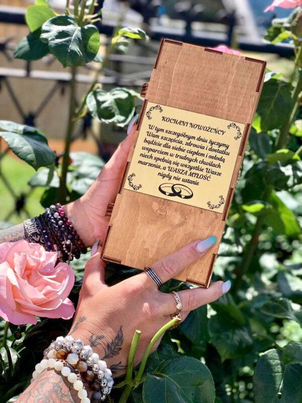 tablica z życzeniami ślubnymi na pudełku drewnianym w żeńskich rękach, kwiaty naokoło