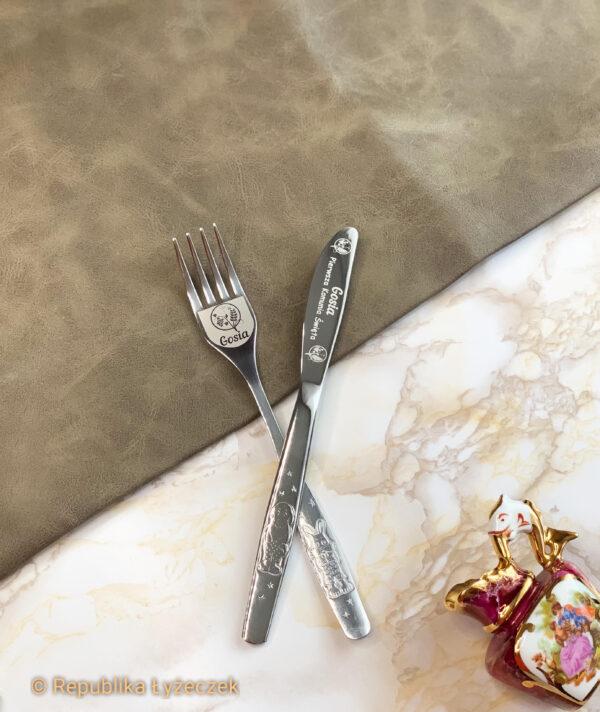 noż i widelec srebnego koloru z grawerem imienia i wzorem komunijnym.obok wazon