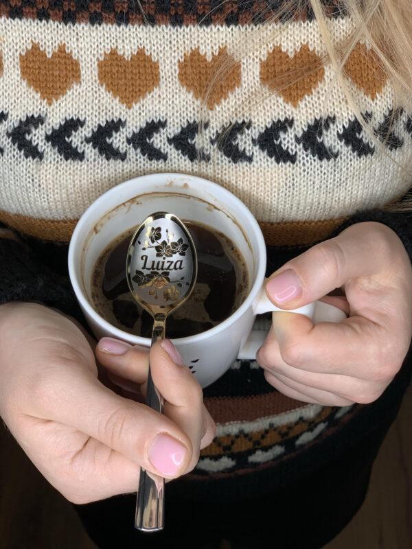 łyżeczka z imieniem Luiza w rękach dziewczyny nad szklanką kawy