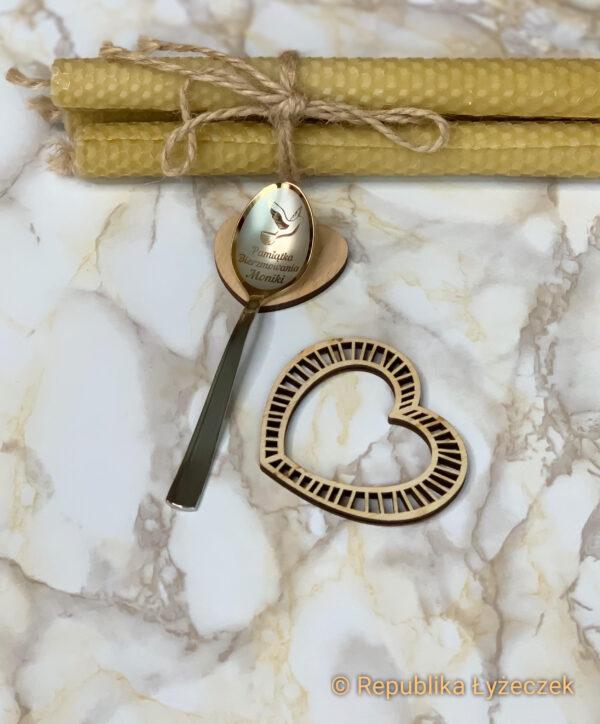 łyżeczka nierdzewna z wygrawerowanym imieniem i symbolem bierzmowania na prezent.obok serduszko drewniane i świece