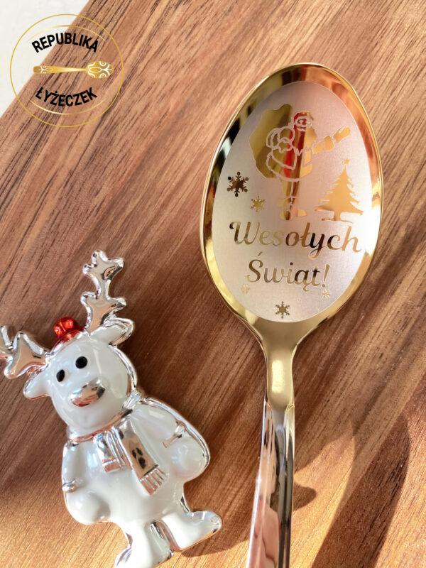 łyżeczka nierdzewna z wygrawerowanym napisem Wesołych świąt na prezent świąteczny,obok dekoracja świąteczna