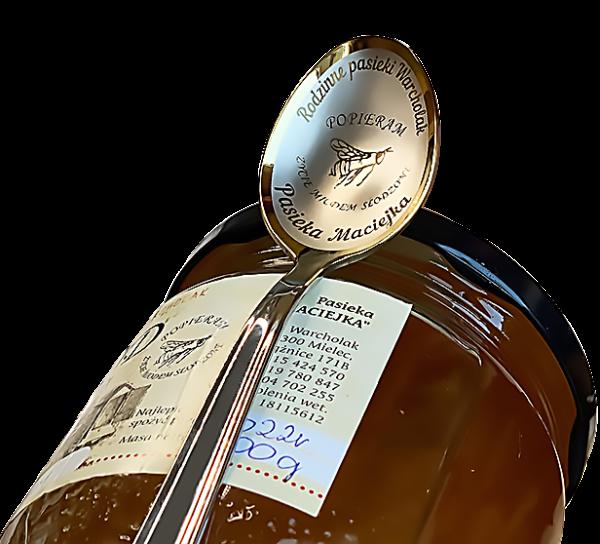 łyżeczka grawerowana na zamówienie z logo pasieki i pszczołą, znaujduje się na słoiku z miodem