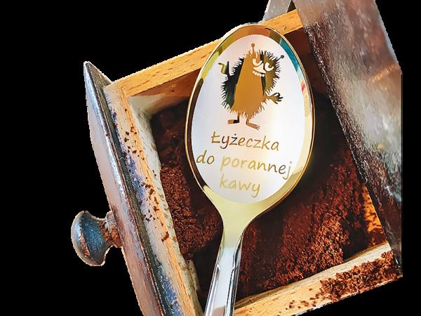 łyżeczka nierdzewna leży na srzryńce z kawą rozsypaną. na łyżeczce grawer potwórka i napis Łyżeczka do porannej kawy